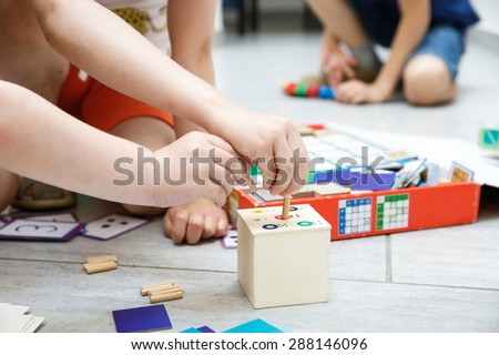 Children playing with homemade, do-it-yourself educational toys. Learning through experience concept.  - stock photo
