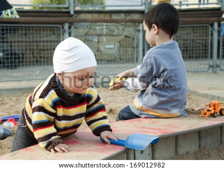 Children playing with sand at sandpit or sandbox at a playground.  - stock photo