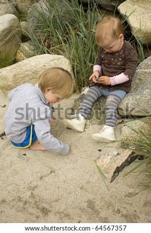 Children playing with sand on a beach - stock photo