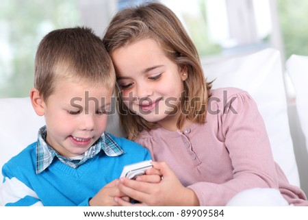 Children playing with smartphone - stock photo