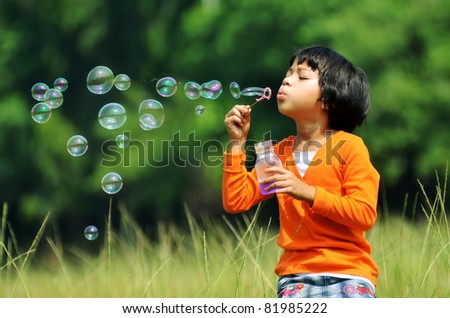 Children playing with soap bubbles on a green environment background - stock photo