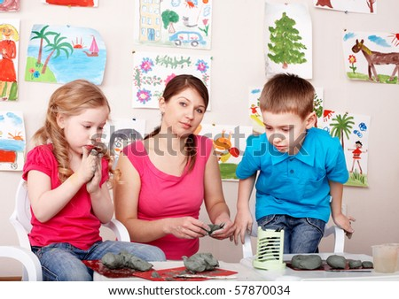 Children playing  with teacher from clay. Child development. - stock photo