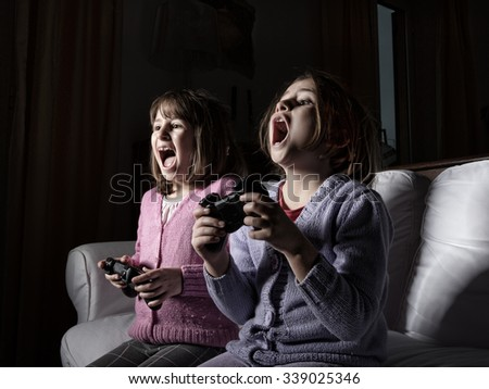 children playing with videogames, living room area - stock photo