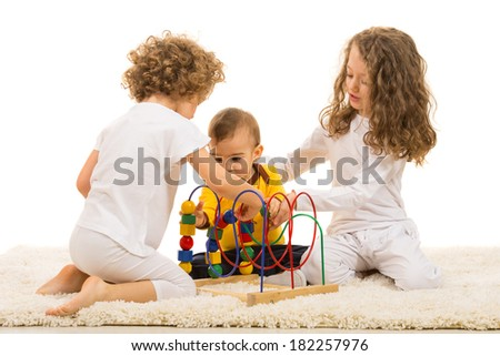 Children playing with wooden toy home and sitting together on fur carpet