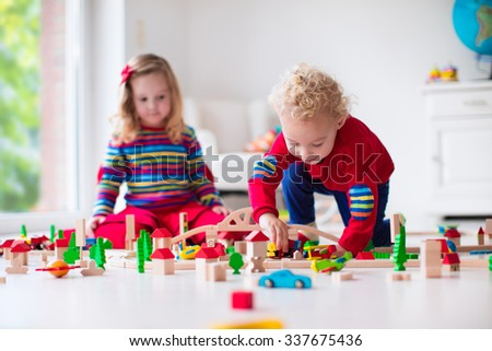 Children playing with wooden train. Toddler kid and baby play with blocks, trains and cars. Educational toys for preschool and kindergarten child. Boy and girl build toy railroad at home or daycare. - stock photo