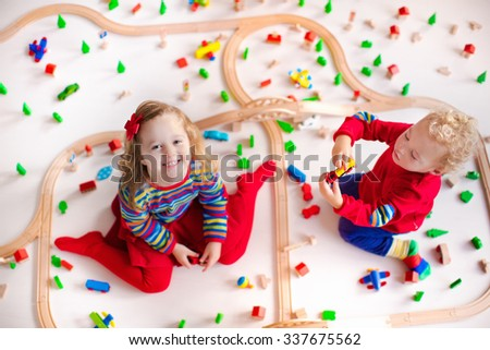 Children playing with wooden train. Toy railroad. Toddler kid and baby play with blocks, trains and cars. Educational toys for preschool and kindergarten child. View from above, kids on the floor. - stock photo
