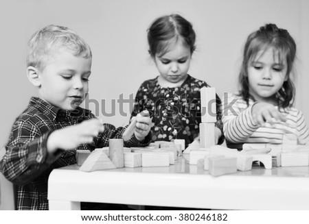 children playing wooden blocks in the kindergarten - stock photo