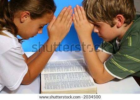 children praying over the bible - stock photo