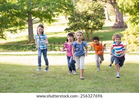 Children racing in the park on a sunny day - stock photo