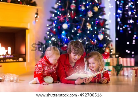 Children read a book and open gifts at fireplace on Christmas eve. Family with child celebrating Xmas. Decorated living room with tree, fire place, candles. Winter evening at home for parents and kids