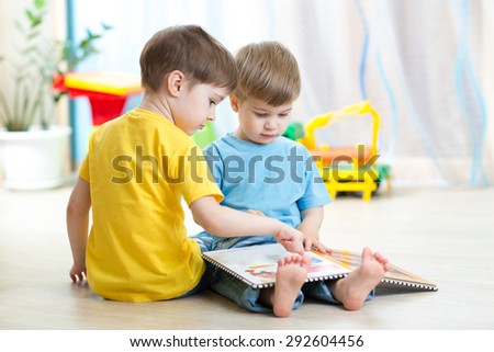 children read a book sitting on floor - stock photo