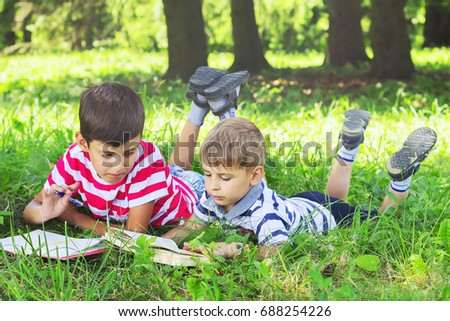 Children  reading a book lying on the grass. Little boy writes in notebook.