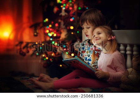 Children reading an interest book sitting on the bed against the decorated Christmas tree - stock photo