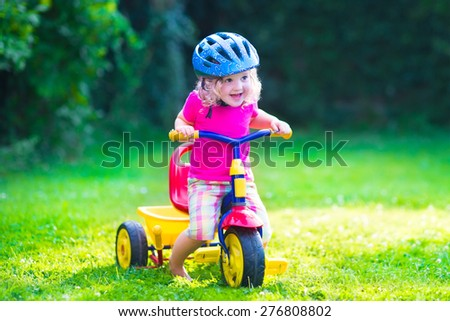Children riding a bike. Kids enjoying a bicycle ride. Little preschooler girl having fun outdoors. Active toddlers play in the garden. Summer fun in a park. Child wearing safety helmet. - stock photo