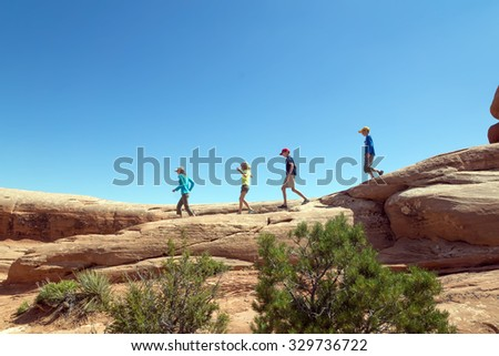 Children run along the red rocks on background blue sky in the Arches National Park, Utah - stock photo