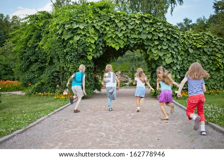Children run on park walkway into arch made of green plants, rear view