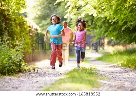 Children Running In Countryside With Father - stock photo