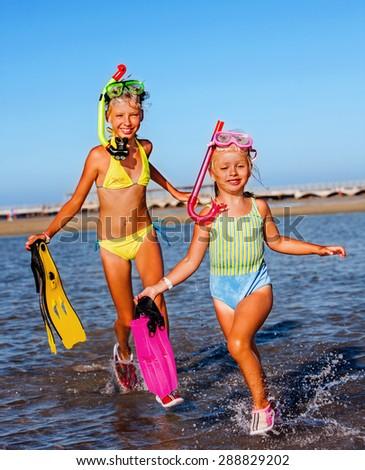 Children running on  beach for snorkeling. - stock photo