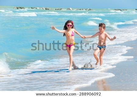 Children running on the beach - stock photo