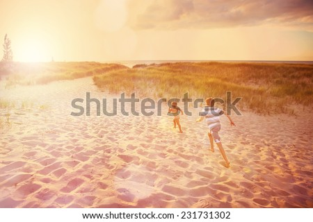 Children running up a dune path to the beach. Some motion blur on running children. - stock photo