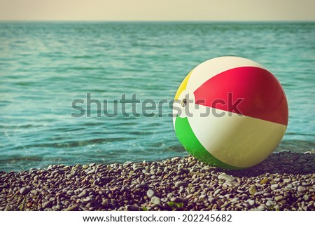 children's ball on the beach against the sea. Toning style instagram - stock photo