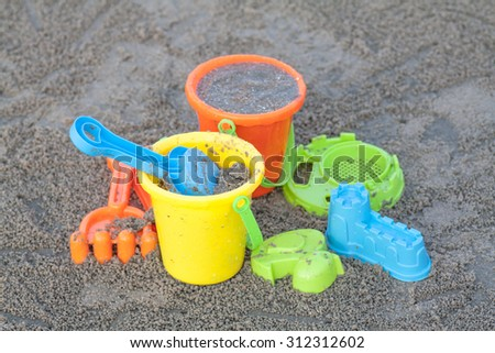 Children's beach toys - buckets, spade and shovel on sand on a sunny day,soft focus when view at full resolution - stock photo