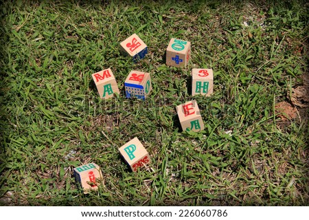 Children's blocks on the grass - stock photo