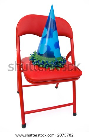 children's chair isolated on white with party hat - stock photo