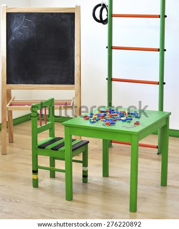 Children's corner in the house. Green table, chair, ladder, chalkboard..Board with space for text - stock photo