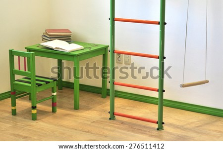 Children's corner with table chair ladder and swings