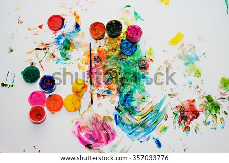 Children's drawing finger paints.children's creativity concept.colored paint smeared on a white background.paints and brush on a white background - stock photo