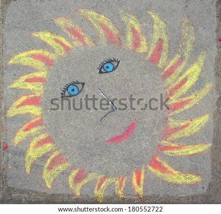 Children's drawing of the sun made colored chalk on the paving - stock photo