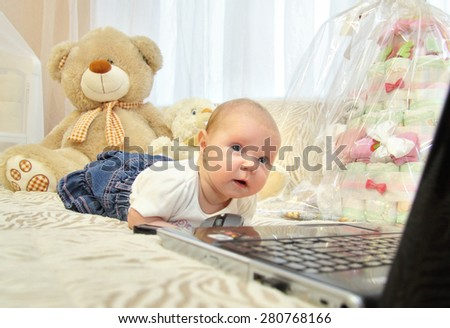 children's emotions.baby on the bed looking at PC