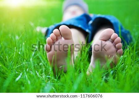 Children's feet  on grass. Family picnic in spring park - stock photo
