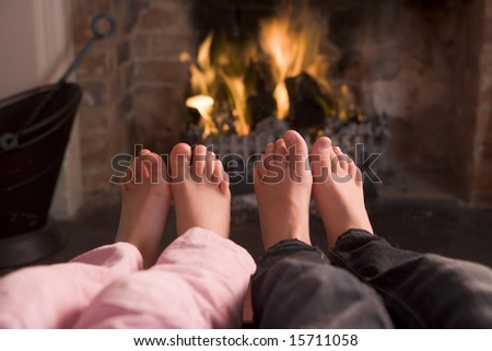Children's feet warming at a fireplace - stock photo