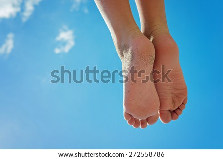 Children's feet with sand against the blue sky with clouds - stock photo