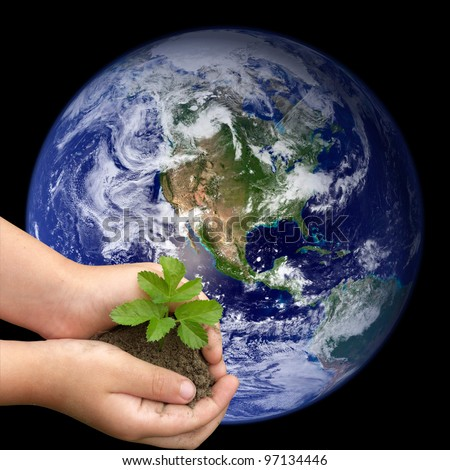 Children's hands holding small plant growing from soil on the background of the world. Elements of this image furnished by NASA - stock photo