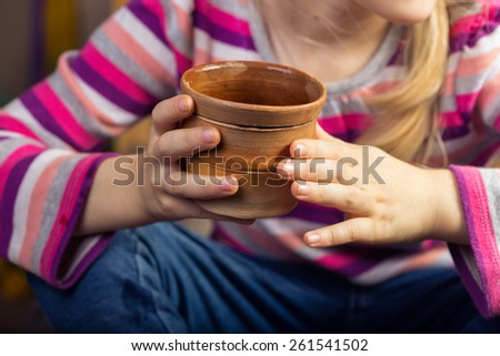 children's hands with a clay cup - stock photo