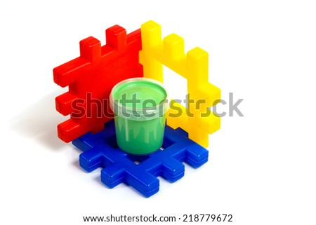 Children's multicolored constructor on which stands the green jar with gouache isolated on white background - stock photo