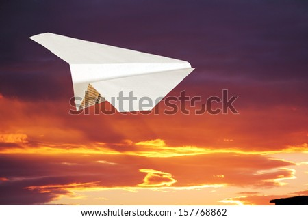 children's paper airplane flying against the sky and clouds. - stock photo