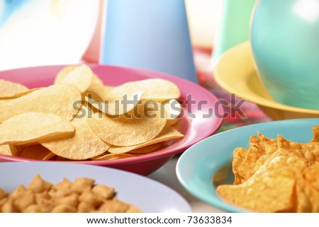 Children's party table with potato chips and nachos in plastic plates with colored balloons in the background - stock photo