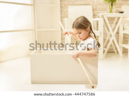 Children's play concept. Happy little girl playing indoor pretending to sail in white wooden box boat with a stick as paddle. Children imagination or creativity concept. - stock photo