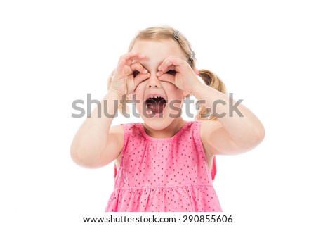 Children's real emotions. Little girl looking through imaginary binocular. - stock photo