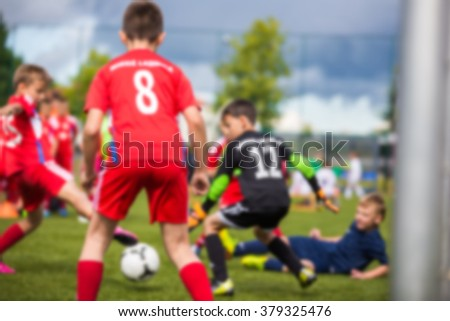 Children's soccer match. Blurred sport soccer football background. Young boys playing football match. Soccer game between blue and red team. - stock photo
