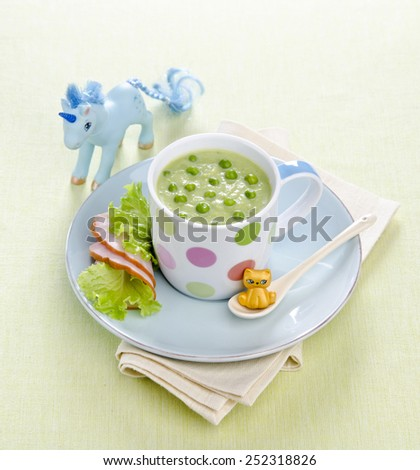 children's soup of green peas in a cup on a blue plate with slices of ham and salad - stock photo