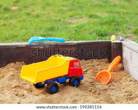Children's toy car in sandbox  - stock photo