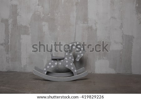 Children's toy horse transport with teddy bear on a gray background Vintage wall of cement. Old texture grunge retro