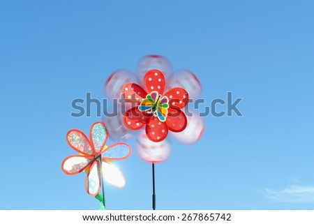 Children's toy (pinwheel) in the shape of a colorful flower whirling in the wind on a clear sunny day, against cloudless blue sky. Concept of joy, happiness and childhood. - stock photo