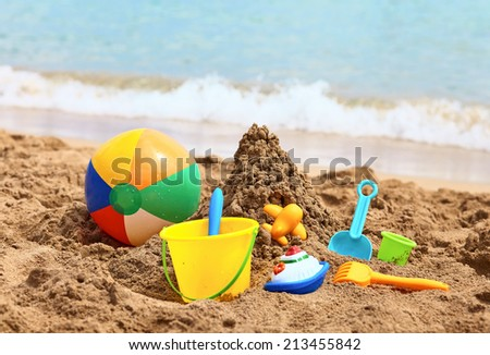 Children's toys on a sand beach - stock photo