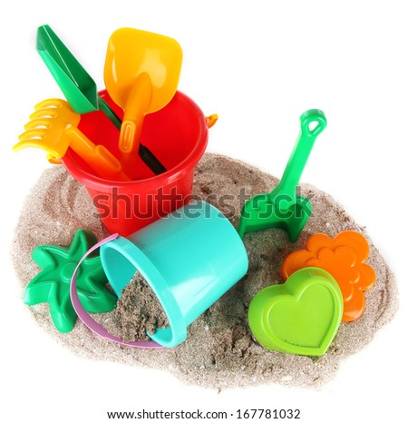 Children's toys on sand isolated on white - stock photo